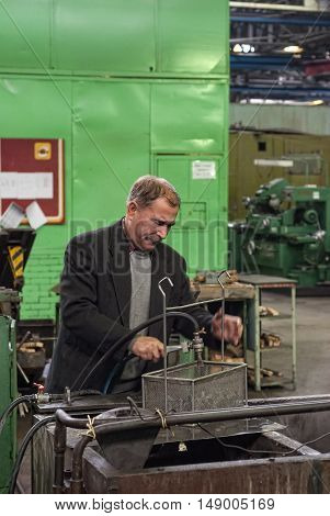 Tyumen, Russia - September 7, 2010: JSC Tyumenskie Motorostroiteli. Plant on production and repair of aviation engines. Mechanic grinds detail on factory