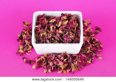 Rose petals in a white bowl on pink background. Dried blossoms, used for perfumes, cosmetics, teas and baths. Purple and orange colored organic herb. Isolated macro photo close up from above.