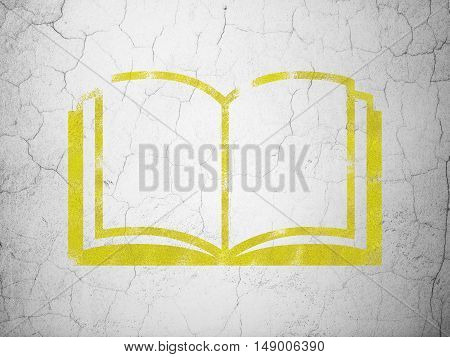 Studying concept: Yellow Book on textured concrete wall background
