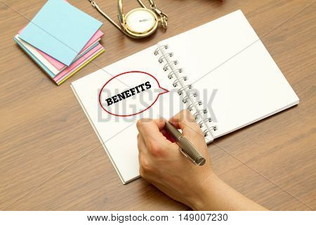 Hand writing BENEFITS word on a notebook with pen.
