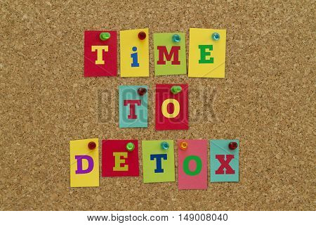 TIME TO DETOX message written on colorful sticky notes pinned on cork board.