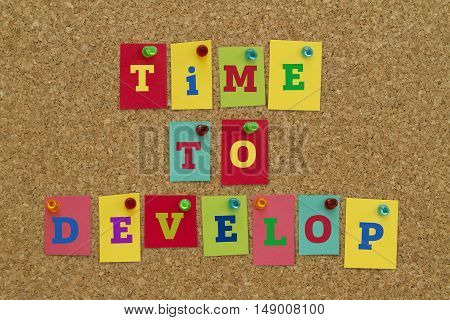 TIME TO DEVELOP message written on colorful sticky notes pinned on cork board.