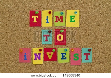 TIME TO INVEST message written on colorful sticky notes pinned on cork board.
