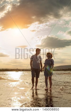Happy Couple Is Walking On The Beach.