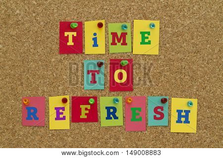 TIME TO REFRESH message written on colorful sticky notes pinned on cork board.