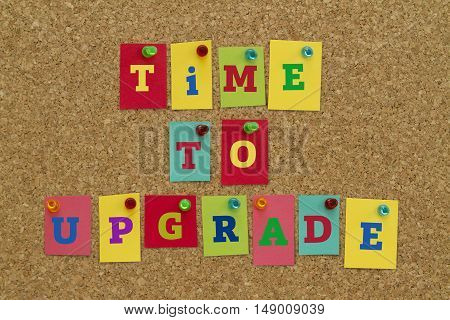 TIME TO UPGRADE message written on colorful sticky notes pinned on cork board.