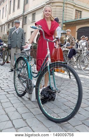 STOCKHOLM - SEPT 24 2016: Bicycle and young woman dressed in old fashioned red dress in the Bike in Tweed event September 24 2016 in Stockholm Sweden