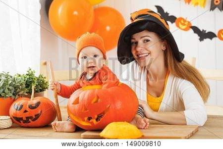family mother and baby son are preparing for Halloween carve a pumpkin and decorate the house