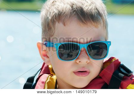 boy in a life jacket and sunglasses outdoor