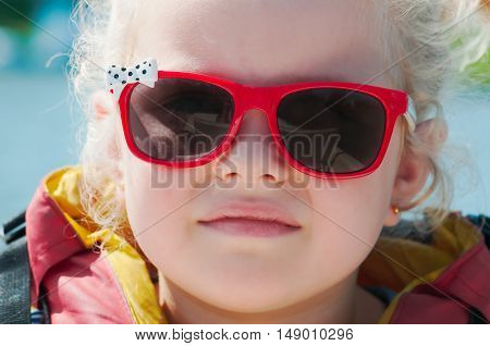 girl in a life jacket and sunglasses outdoor