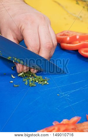 Male hand crushed herbs on an old blue glass cutting board