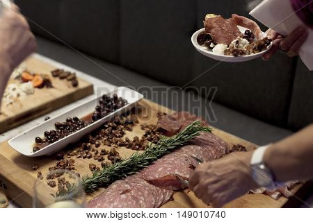 A woman makes her selection from a meat and cheese charcuterie board.