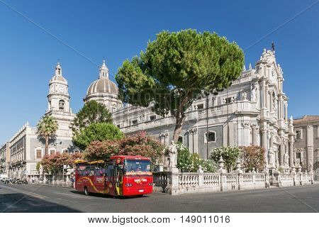CATANIA, ITALY - JUL 25 , 2012: Catania town main square center with the Cathedral of Santa Agatha and a sightseeingbus in Sicily, Italy