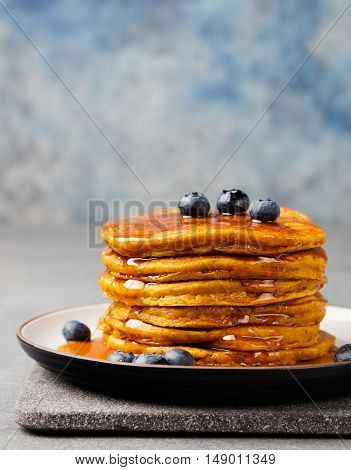 Pumpkin pancakes with maple syrup and blueberries on a plate Grey stone background Copy space