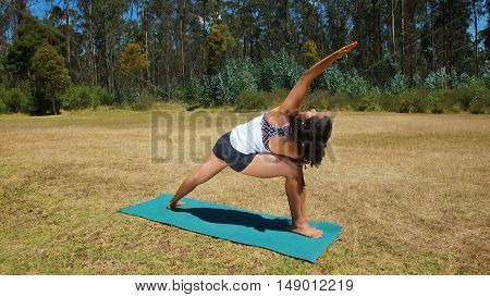 Young latin woman doing yoga in the park on yoga mat