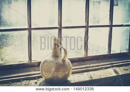 Retro filtered an old dusty clay bottle by a window.