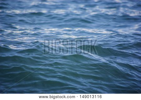 Blue sea water surface background at sunset with waves