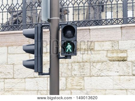 Traffic light on the background of the street. Steady green color. Close-up.
