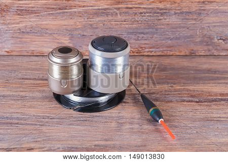 Fishing tackle - reels with fishing line and float on wooden background