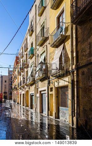 Wet sunny street early morning in Tarragona, summer Spain