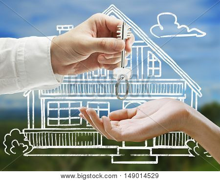 Businessman handing key to female on landscape background with creative house sketch. Real estate and mortgage concept
