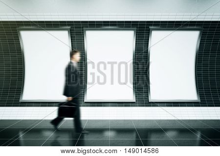 Blurry businessman walking in front of three empty ad posters in metro station with dark tile walls. Mock up 3D Rendering