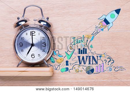 Silver alarm clock and creative rocket ship and business icons sketch on wooden background. Start up concept