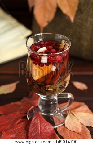 Autumn hot tea with lemon spices in glass cup falling leaves around