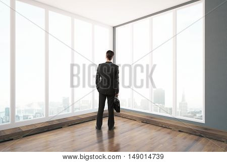Back view of young businessman with briefcase standing in unfurnished interior with wooden floor and panoramic windows with city view. 3D Rendering
