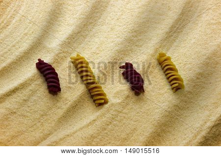 some color pasta on the yellow flour