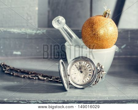 Silver clock on chain near white glass bowl and orange glitter christmas decorative ball on grey wooden background closeup