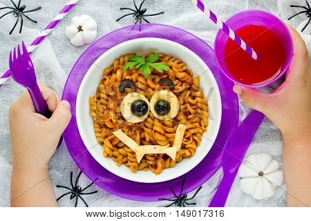 Baby eating funny and healthy meal concept. Pasta bolognese on Halloween party recipe for kids to dinner or lunch edible cute monster face from fusilli in sauce top view of empty space for text