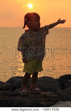 Japanese girl standing by the seaside in red (1 year old)