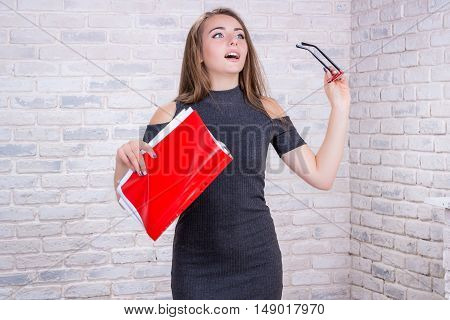 Young beautiful girl model with long hair imitates business lady office manager or administrator with red folder of documents