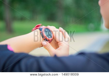 Young fitness girl checks stopwatch tracker on her wrist during running outdoor