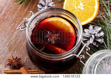 Christmas drink with orange fruit anise cinnamon and cloves on wooden table