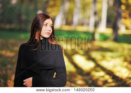 Portrait of a cute long-haired girl in an elegant black cardigan on a sunny day in the park in autumn.