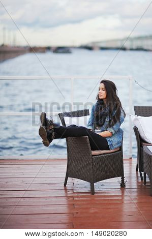 Beautiful Brunette In A Blue Denim Jacket And A Black Scarf Sitting In A Chair On The Pier, With Dow