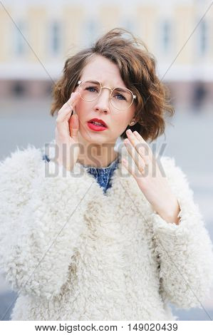 Young Beautiful Girl Student In A White Jacket In The Town Square With Narrowed Eyes Looking Through