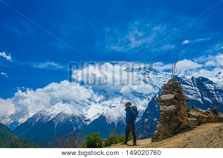 Photo Man Traveler Backpacker Mountains Way.Young Guy Looking Away Take Rest Sunny Terrace Path.Snow Landscape Background. Horizontal