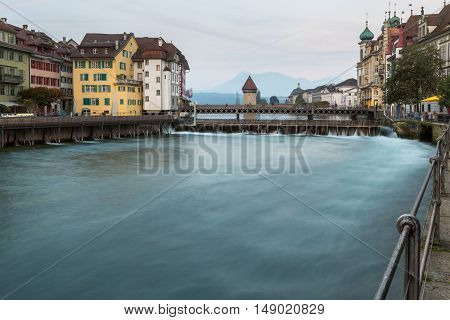 Waterfront view of Lucerne Switzerland at dusk with colorful historic townhouses overlooking an old bridge and weir on Lake Lucerne