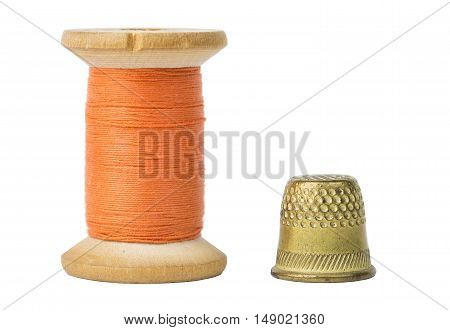 Orange thread spool and thimble isolated on white background.