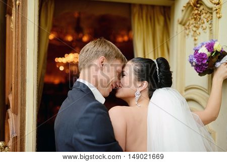 Wedding couple indoors is hugging each other. Beautiful model girl in white dress. Man in suit. Beauty bride with groom. Female and male portrait. Woman with lace veil. Cute lady and handsome guy