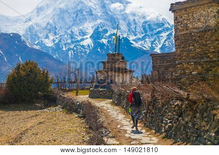 Young Pretty Woman Wearing Red Jacket Backpack Trail Mountains.Mountain Trekking Rocks Path Village. Snow Landscape View Background. Horizontal Photo