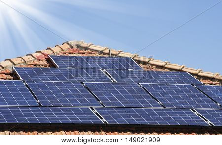 Solar panels on a roof with sun rays