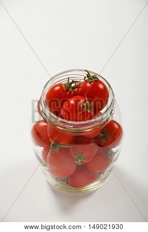 Cherry Tomatoes In Glass Jar Over White