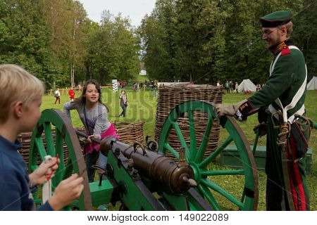 GATCHINA, ST. PETERSBURG, RUSSIA - SEPTEMBER 10, 2016: Girl rams the ball into the cannon during the festival Gatchinskaya Byl. The festival is held first time this year