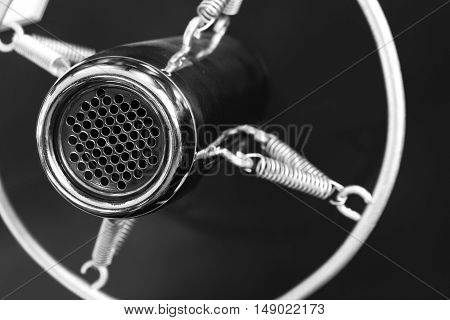 Vintage retro style old metal professional studio vocal voice and music recording microphone suspended with spiral round frame close up black and white