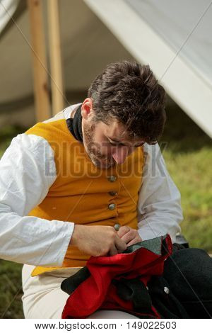 GATCHINA, ST. PETERSBURG, RUSSIA - SEPTEMBER 10, 2016: Soldier mends his uniform in the camp during the festival Gatchinskaya Byl. The festival is held first time this year
