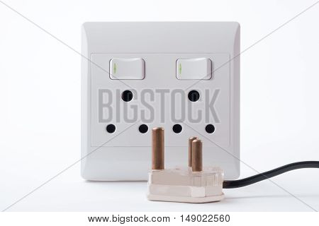 South African Electric Double Wall Plug with a three point plug lying in front of it.